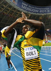 Bolt of Jamaica celebrates with his national flag after winning the men's 100 metres final during the IAAF World Athletics Championships at the Luzhniki stadium in Moscow