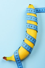 Banana and blue measuring tape on light blue background