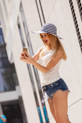 Young woman taking selfie with smartphone outside