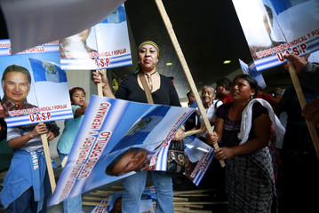 Supporters of former Guatemalan President Alfonso hold signs with images of the former president, outside La Aurora airport in Guatemala City