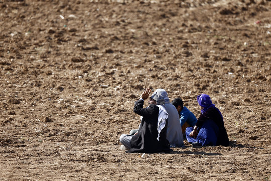 Man sitting with his Kurdish refugee family from Syrian town of Kobani looks up into the sky for airplanes as they sit in a field near Mursitpinar border crossing, on Turkish-Syrian border in southeastern town of Suruc in Sanliurfa province