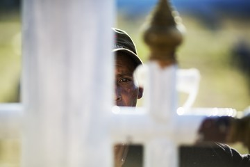 A worker paints flag poles at the Tsunami Victims Cemetery outside Ban Nam Khem in Phang Nga province