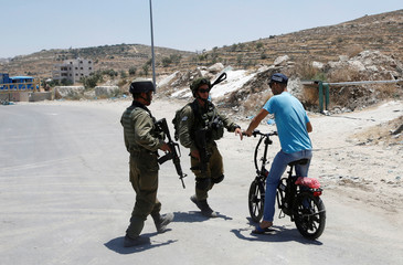 Israeli soldiers stop a Palestinian on his bicycle at the entrance of Yatta near the West Bank city of Hebron