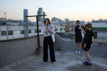 Women take pictures as they stand on roof of workshop in industrial district of Mullae in Seoul