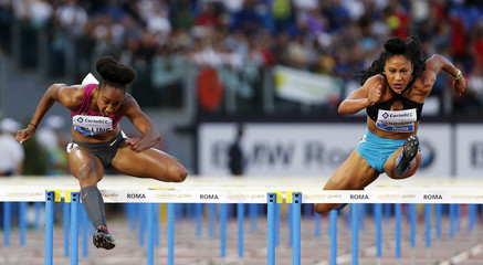 Rollins of the U.S. competes next to her compatriot Harrison in the women's 100m hurdles event during during the Golden Gala IAAF Diamond League at the Olympic stadium in Rome