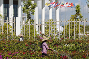 Women water flowers near the main venue for the Association of Southeast Asian Nations (ASEAN) summit in Naypyitaw