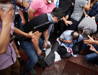 People help a man who was attacked by a water cannon during protests at Kizilay square in central Ankara