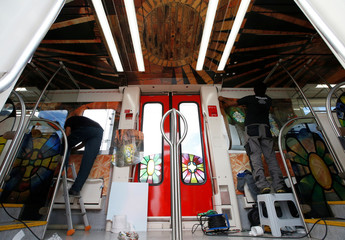 Workers decorate a train cabin to promote the unfinished church Colonia de Guell, where Gaudi's crypt is located, in Martorell