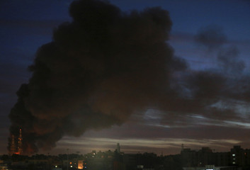 Black smoke billows in the sky above areas where clashes are taking place between pro-government forces and the Shura Council of Libyan Revolutionaries who have joined forces with the Islamist group Ansar al-Sharia, in Benghazi
