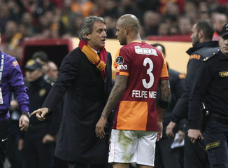 Galatasaray's coach Mancini talks with player Melo during their Turkish Super League derby soccer match against Fenerbahce at Turk Telekom Arena in Istanbul
