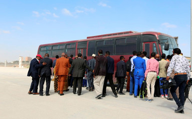 Somali lawmakers and journalists board a chartered bus to the venue of the elections during the presidential vote at the airport in Somalia's capital Mogadishu