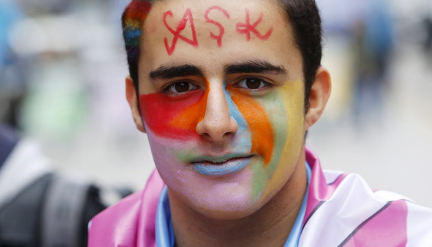 """An LGBT activist adorns his forehead with the word """"ask"""" (which means love), as he participates in a protest against Turkey's ruling AK Party (AKP) in Ankara"""