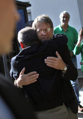 Colombian presidential candidate Antanas Mockus embraces a supporter as he leaves his house to cast his vote in Bogota