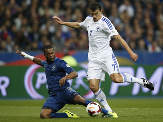 France's Evra challenges Finland's Eremenko during their 2014 World Cup qualifying soccer match at the Stade de France stadium in Saint-Denis