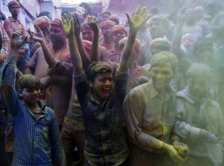 Hindu devotees cheer as they throw coloured powder on bystanders near the Bankey Bihari temple during Holi celebrations in Vrindavan
