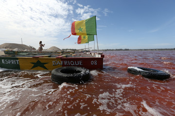 A tourist takes a photograph next to packed boats on the bank of Lac Rose in Senegal