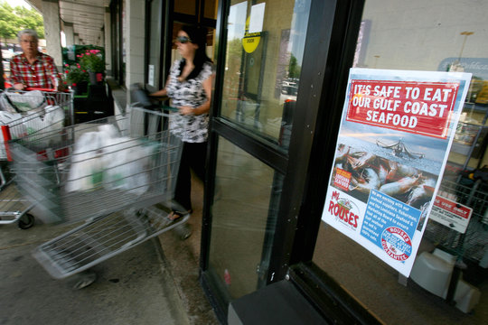 Shoppers walk past a sign at a local grocery store in Metairie, Louisiana advertising safe seafood from the Gulf Coast