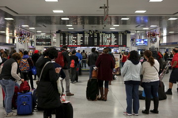 Travelers with suitcases wait for trains in Pennsylvania Station in Manhattan
