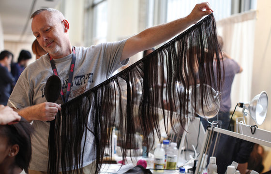 A stylist holds human hair extensions backstage before the Made in Africa: by ARISE Magazine Spring 2012 show during New York Fashion Week