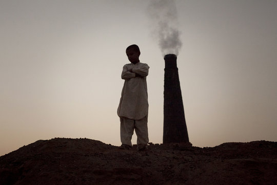 Ahsan, 12, stands looking over an oven at a brick yard in the outskirts of Islamabad