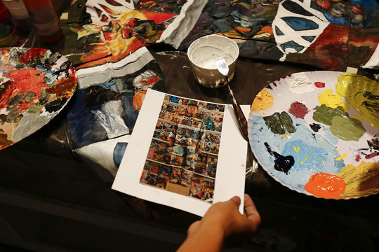 A picture of Chinese artist Liu Bolin standing partially blended into the background is seen on a table in Caracas