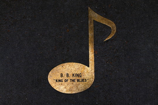 A brass music note imbedded into the sidewalk along Beal street is shown