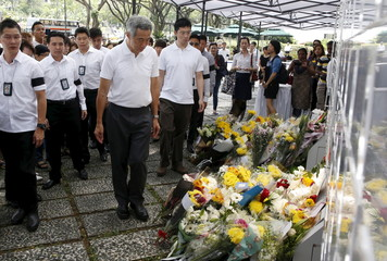 Singapore's Prime Minister Lee Hsien Loong looks at flowers placed in tribute to the late former prime minister Lee Kuan Yew outside the Istana in Singapore