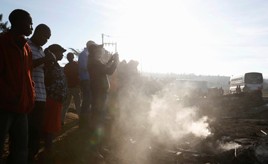 Residents stand in the smoke as they assess the wreckages of cars burnt after a fireball from an tanker engulfed several vehicles and killed several people, near the Rift Valley town of Naivasha, west of Kenya's capital Nairobi