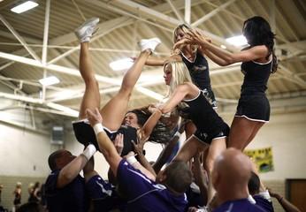 A Baltimore Ravens cheerleader falls during a stunt at cheerleader training camp at Deep Creek