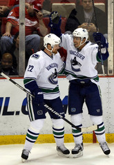 Vancouver Canucks center Ryan Kesler celebrates with teammate Daniel Sedin after scoring a goal against the Detroit Red Wings during the first period of their NHL hockey game in Detroit