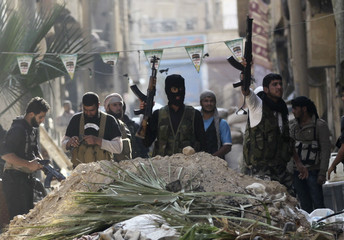 Free Syrian Army fighters hold up their weapons as they stand behind a pile of sand in Deir al-Zor, eastern Syria