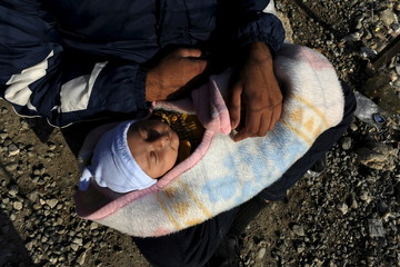 A migrant man holds a baby inside a refugee camp as refugees and migrants wait to cross Greece's border with Macedonia near the Greek village of Idomeni
