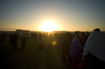 Revellers gather as they enjoy the sunrise during the winter solstice at Stonehenge on Salisbury Plain in southern England
