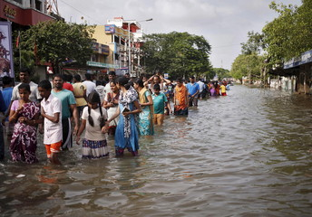 Residents wade through a flooded street as they evacuate their homes in Chennai