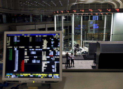A videographer films an electronic board showing the Japan's Nikkei average and related indexes is seen next to a computer showing the market indexes at the Tokyo Stock Exchange  in Tokyo