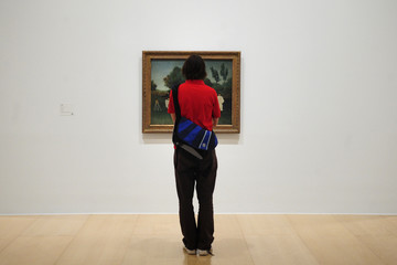 """A visitor looks at a Henri Rousseau painting during the presentation of the exhibition """"Henri Rousseau"""" at the Guggenheim Museum in Bilbao."""