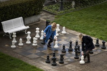 Russian journalists play a game of giant chess in a courtyard at the Beau Rivage Palace Hotel in Lausanne