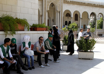 Agents of parliamentary candidates wait for voters in front of a polling station in Damascus