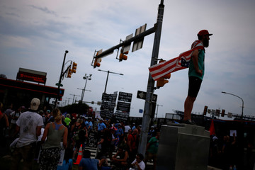 Man wears American flag as cape near site of 2016 Democratic National Convention in Philadelphia, Pennsylvania