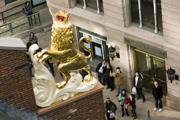 People stop to watch and take photos after crews installed a statue of a lion on top of the Old State House in Boston