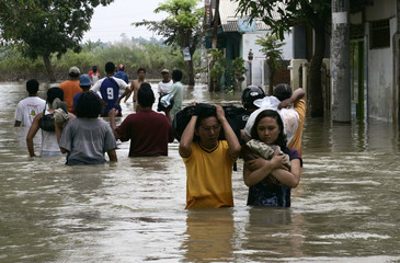 Residents walk as they evacuate their flooded village in Karawang, West Java province