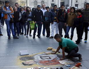 A man draws on the sidewalk a chalk painting of Chile's soccer player Jara and Uruguay's Cavani as people watch in Santiago