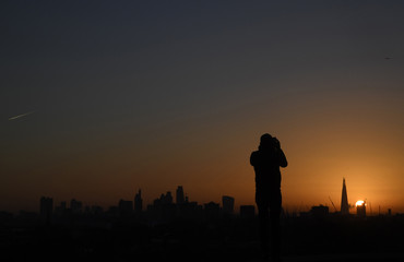 A man takes photographs of the City of London at sunrise in London, Britain