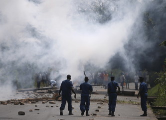 Policemen walk after they fire tear gas canisters at protesters during a protest against Burundi President Pierre Nkurunziza and his bid for a third term in Bujumbura