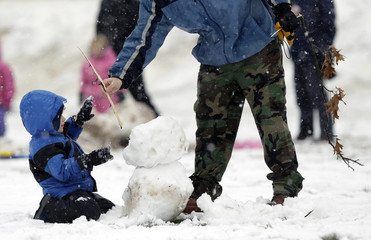 Little boy gets stick from father for snowmans arm in Takoma Park Maryland