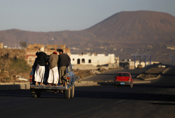 People travel on the back of a car on a highway near Sanaa
