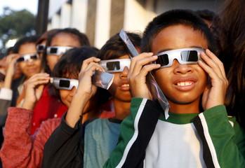 School children watch a solar eclipse outside the planetarium in Jakarta, Indonesia