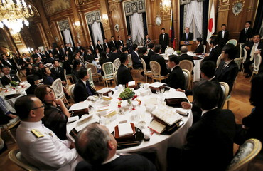 Philippine President Aquino delivers a speech as Japan's Prime Minister Abe listens during a banquet hosted by Abe at the state guest house in Tokyo