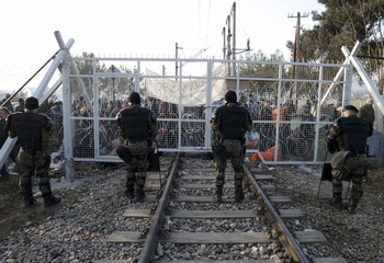 Macedonian policemen stand in front of a gate over rail tracks as migrants wait behind at the Greek-Macedonian border