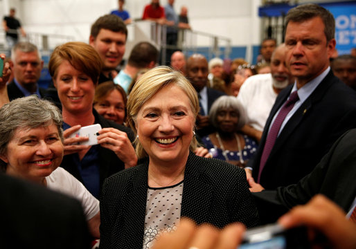 U.S. Democratic presidential nominee Hillary Clinton smiles while taking pictures with supporters at Futuramic Tool & Engineering in Warren